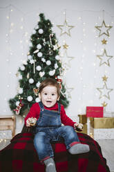 Cheerful baby boy with mouth open playing while sitting at home during Christmas - EBBF01698