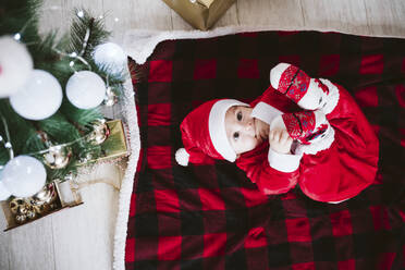 Cute baby boy wearing Santa Claus costume lying on blanket at home during Christmas - EBBF01701