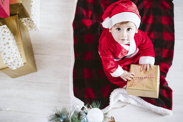 Cute baby boy in Santa Claus costume playing with gift box while sitting at home during Christmas - EBBF01704