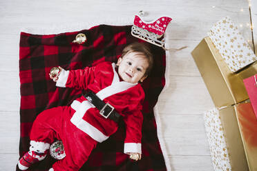 Smiling baby boy in Santa Claus costume lying on blanket at home during Christmas - EBBF01707