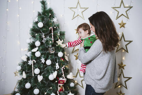 Mother carrying son while standing by tree at home during Christmas - EBBF01713