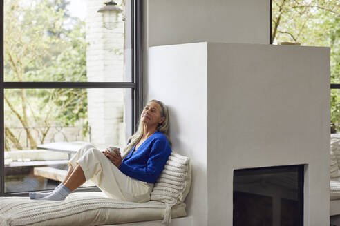Mature woman with coffee cup day dreaming while leaning on wall of fireplace at home - MCF01521