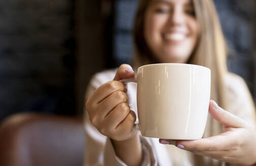 Woman holding coffee cup while sitting at cafe - JCCMF00106