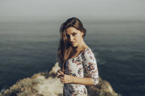 Young woman staring while standing against sea - MTBF00754