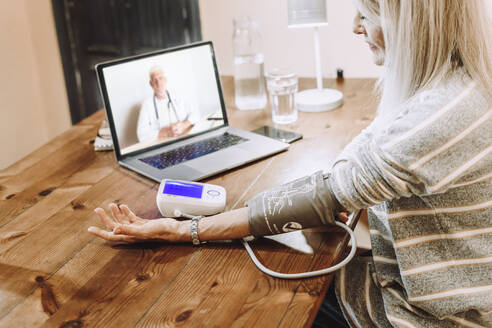 Senior woman checking own blood pressure under guidance of doctor on video call at home - ERRF04824