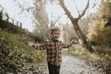 Carefree boy standing with arms outstretched in forest - GMLF00882