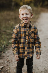 Smiling boy wearing plaid shirt standing on footpath in forest - GMLF00891