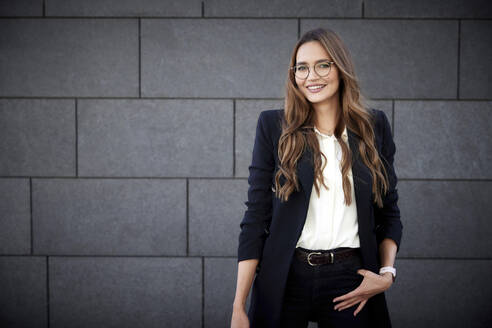 Smiling female entrepreneur standing with hands in pockets against brick wall - RHF02462