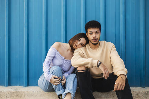 Girlfriend leaning on boyfriend's shoulder while sitting against blue wall - MIMFF00296