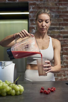Mature woman pouring raspberry fruit smoothie in glass at kitchen - VEGF03302