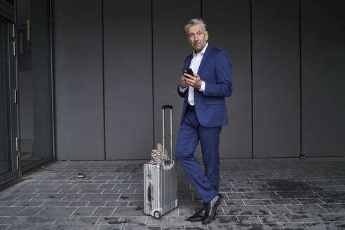 Businessman using mobile phone while standing with luggage on footpath - SDAHF01019
