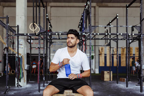 Young man holding water bottle while sitting on box at gym - MARF00014