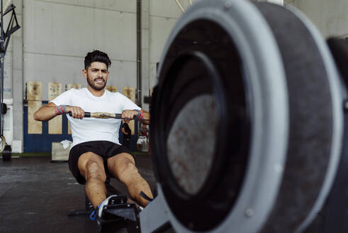 Athlete exercising with rowing machine at gym - MARF00020