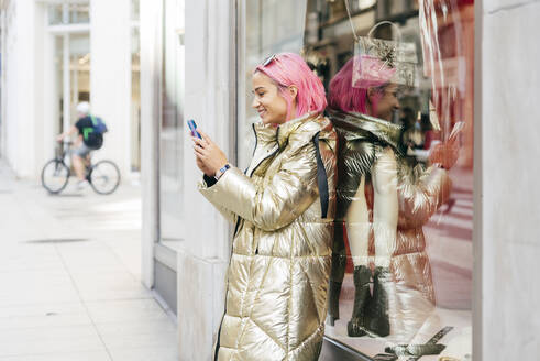 Smiling woman using mobile phone while leaning on store window - MARF00026