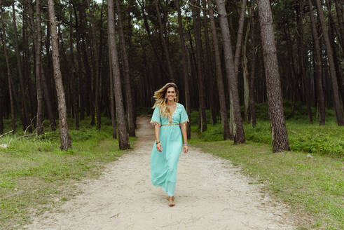 Mid adult woman smiling while walking on forest path - MARF00028