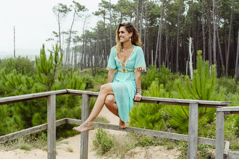 Woman smiling while sitting on railing at forest - MARF00031