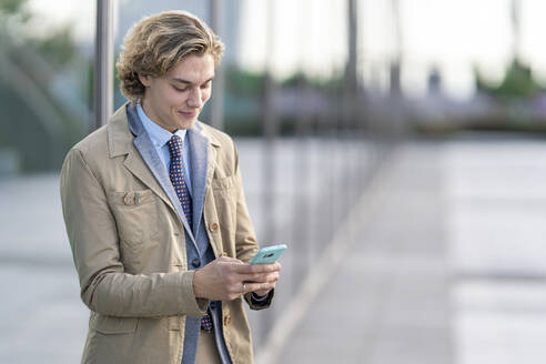 Young businessman using mobile phone while standing outdoors - GGGF00435