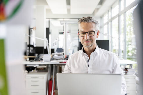 Smiling businessman working on laptop in office - PESF02416