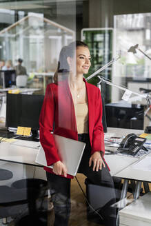 Smiling businesswoman with laptop looking away while leaning on desk at office - PESF02431