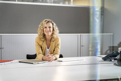 Smiling female entrepreneur leaning on desk at work place - PESF02443