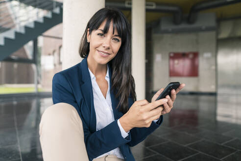 Smiling businesswoman holding smart phone while sitting in office lobby - JOSEF02565