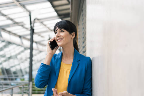 Businesswoman talking on mobile phone while leaning by wall at office - JOSEF02598