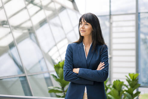 Thoughtful businesswoman with arms crossed looking away in office - JOSEF02631