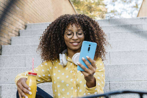 Smiling woman with headphones and drink using mobile phone while sitting on steps - XLGF00819