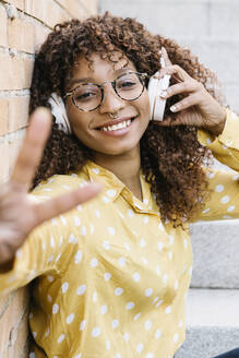 Happy woman with headphones showing peace gesture while sitting on steps - XLGF00825