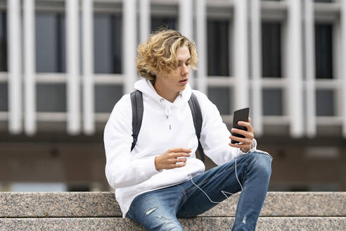 Young man using mobile phone while sitting on staircase - GGGF00450