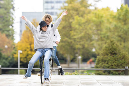 Carefree woman sitting with male friend on bicycle in park - GGGF00459