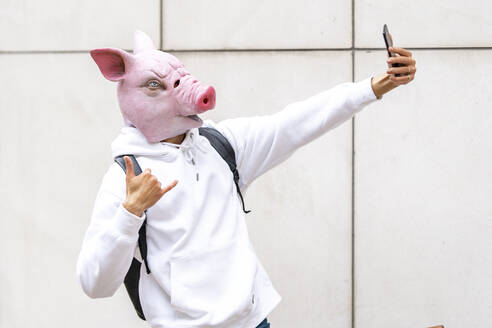 Man with pig mask taking selfie on smart phone against wall - GGGF00474