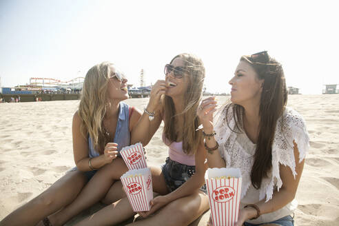 Smiling friends eating popcorn at beach on sunny day - AJOF00961