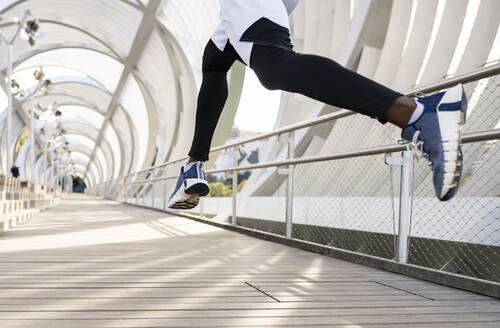 Athlete wearing sports shoe running on walkway - JCCMF00151