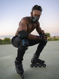 Sportsman wearing protective face mask and roller skate crouching on ground - JCCMF00169