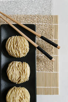From above of round Asian noodles and wooden chopsticks arranged on bamboo mat on table in cafe - ADSF19110