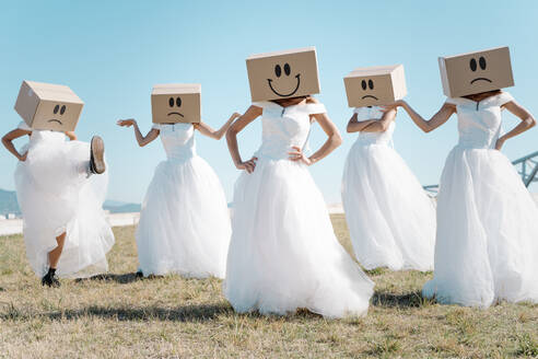 Full body of women wearing bridal dresses and boxes with happy and sad smileys on head standing in field - ADSF19158
