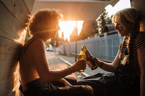 Young female couple toasting with beer bottles in back of van - CUF56607