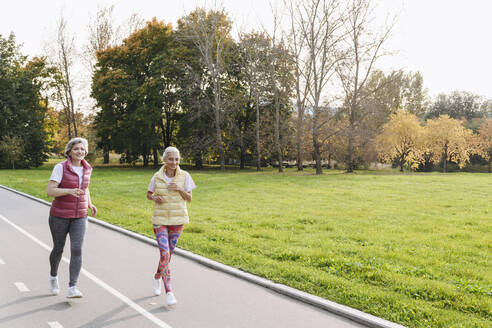 Smiling female friends jogging in public park on sunny day - VYF00353