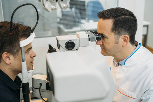 Mature optometrist examining patinet's eye through phropter in clinic - MPPF01299