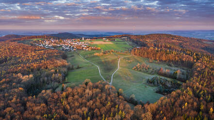 Germany, Baden-Wurttemberg, Drone view of village surrounded by autumn forest at dawn - STSF02719
