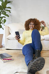 Happy businesswoman with hand in hair holding mobile phone while sitting on floor at home - VEGF03313