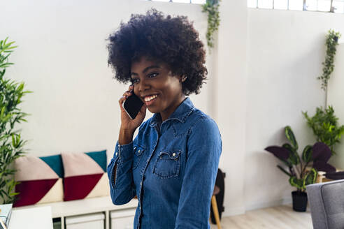 Young woman smiling while talking on mobile phone at home - GIOF09990