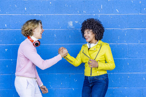Cheerful multi ethnic friends laughing while holding hand against blue wall - GGGF00480