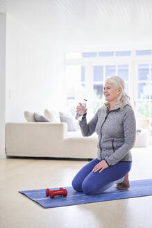 Smiling woman having water while exercising with dumbbells in living room - JAHF00011