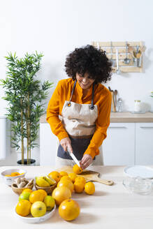 Young woman cutting orange for making juice while standing in kitchen at home - GIOF10043