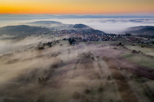 Germany, Baden-Wurttemberg, Berglen, Drone view of village shrouded in thick fog at dawn - STSF02738