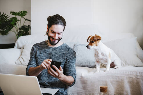 Man with laptop using mobile phone while sitting by dog at home - EBBF01784
