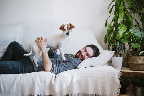 Happy man smiling while playing with pet lying on sofa at home - EBBF01796