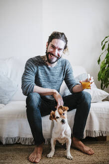 Smiling young man holding juice glass while sitting with dog on sofa at home - EBBF01814